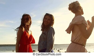 group of happy women or girls dancing on beach - summer...