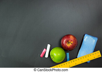 Back to school - Apples and stationery on chalkboard with...