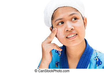 Woman applying moisturizer cream on her pretty face