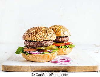 Fresh homemade burgers on wooden serving board with onion rings.
