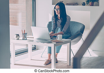 Time to work. Confident young beautiful woman working on laptop while sitting at her working place