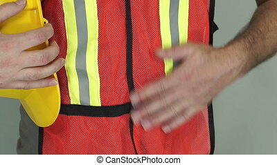 Industrial Man Adjusts Safety Vest - Close up shot of an...