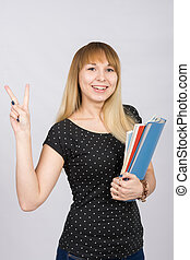 The joyful girl with a folder in his hands shows gesture...