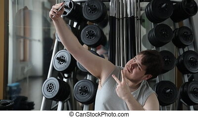 Fat guy in the gym doing selfie Behind his back is a stand...