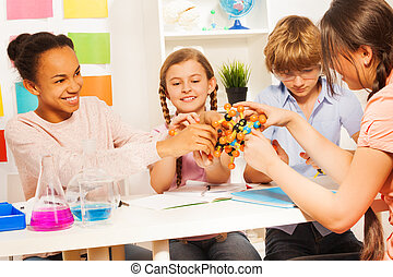 Kids assembling molecule model for science project - Team of...