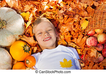 Smiling boy laying on the leaves with pumpkins - Smiling boy...