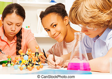 Three students writing chemical formula at class - Three...