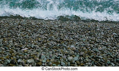 Pebble beach and sea. The waves rolled on shore, water...