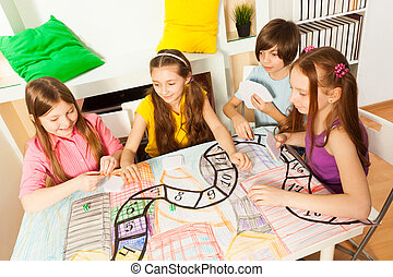 Top view of four kids playing the tabletop game - Top view...