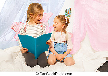 Two little pixies with wings reading bedtime story - Two...