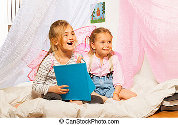 Two little smiling pixies reading the fairy-tale - Two...
