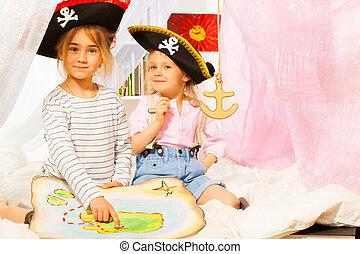 Two little girls playing pirates with treasure map - Two...