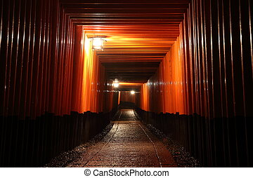 Tori gates in Fushimi Inari Shrine at night with selective...