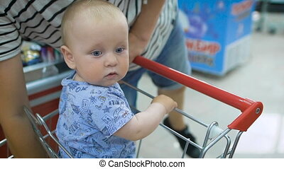 Little baby sitting in a grocery cart in a supermarket,...