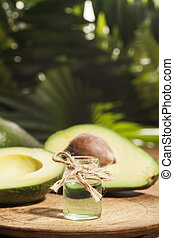 Avocado Essential Oil on tropical green leaves background...