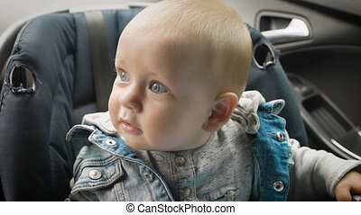 In car safety for children. Little boy sitting in a special...
