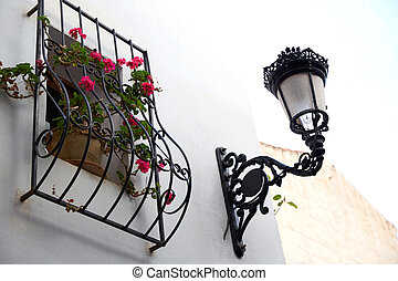 Benidorm white facade window with flowers pot and...
