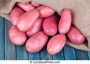 red potatoes on a blue wooden table - red potatoes in burlap...