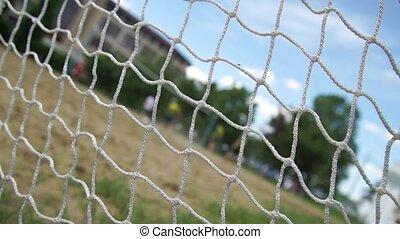 Beach football trough the goal net on cloudy sky background...