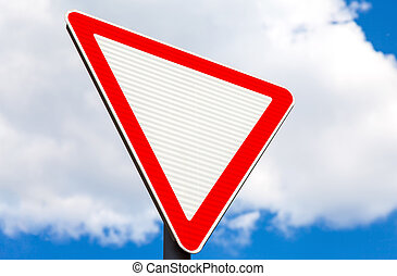 Give way traffic sign above cloudy sky