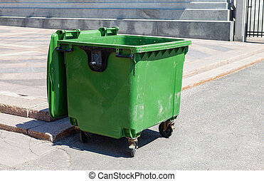 Opened green plastic recycling container at the sunny city street