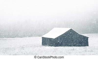 Barn With Snow Falling - Barn in field covered in heavy...