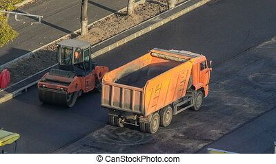 Workers operating asphalt paver machines during road...