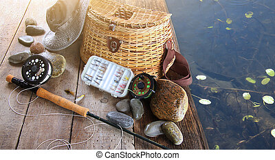 Close-up of fishing equipment and hat at the lake