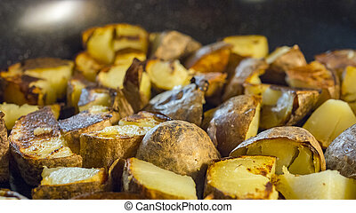 Roasted potato in a frying pan on wooden table - Alot of...