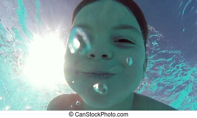 Boy in pool - Cute teen boy dives in blue pool with open...