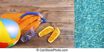 Summer fun background with flip flops, towel and goggles