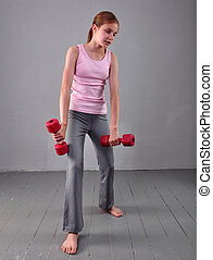 Teenage sportive girl is doing exercises to develop with dumbbells muscles on grey background. Sport healthy lifestyle concept. Sporty childhood. Teenager exercising with wieghts.