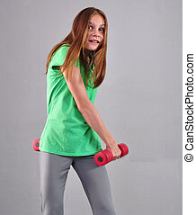 Teenage sportive girl is doing exercises to develop muscles on grey background. Sport healthy lifestyle concept. Sporty childhood. Teenager exercising with wieghts.