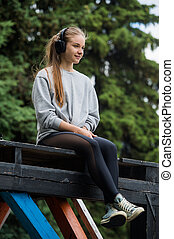 Cheerful athletic woman sitting resting after exercise in the park on the bench with phone and headphones