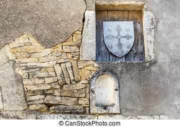 Old stone wall with niches and wooden shield stamp in one of...