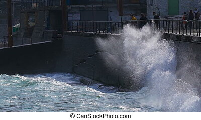 Strong waves breaking on the stone slabs waterfront. People...