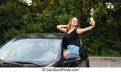 Young woman taking selfie picture in car - Smiling young...