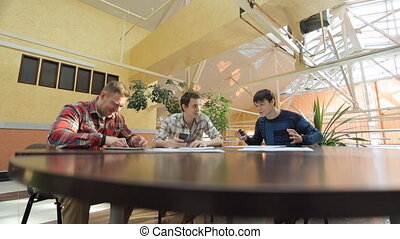 Three men at table, hold smart phone, use tablet computer, stylish device