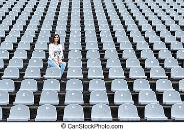 Lonely woman on the stadium - Lonely beautiful woman sitting...