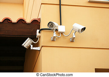 Security camera on yellow wall of house.