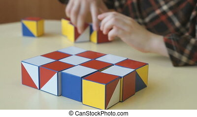 A boy collecting a pattern using colored cubes - The little...