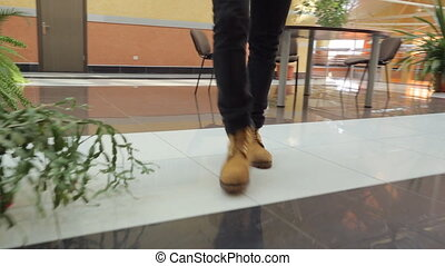 Man in yellow boots walks throughout business center. Step...