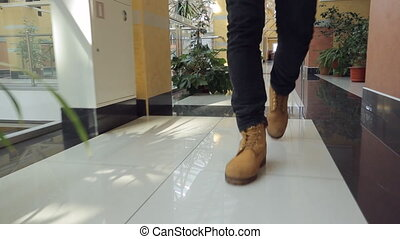 Legs of man in leather brown shoes walk inside corridor.