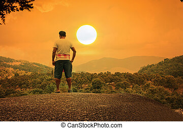 Young man standing on the stone at mountain sunset background