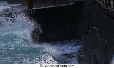 Strong waves breaking on the stone slabs waterfront.