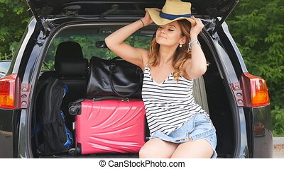 Girl in the trunk of a car with suitcases - Travel, tourism...
