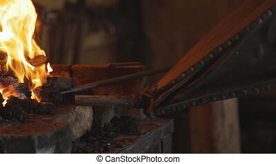 Blacksmith using a leather bellows fanning coals and pulls out a red hot billet.