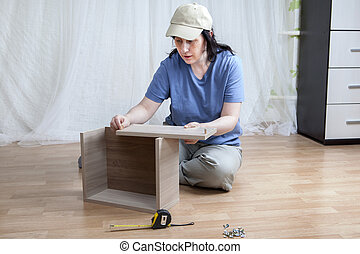 One Caucasian girl mounts new furniture while sitting on...