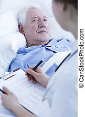 Nurse interviewing elderly patient - Nurse or doctor...