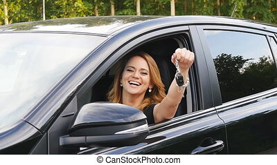 Woman driver holding car keys driving her new car. Beautiful...